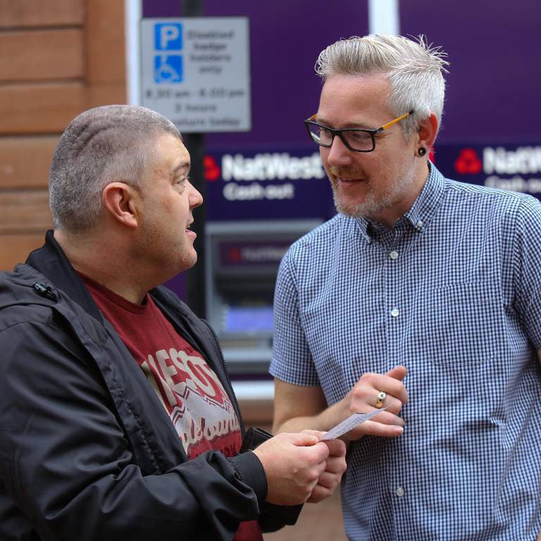 A service user chats to a support worker in the street