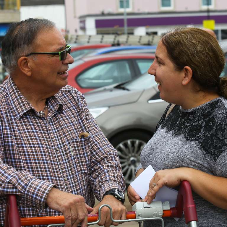 A service user and a support worker chat over a shopping trolley