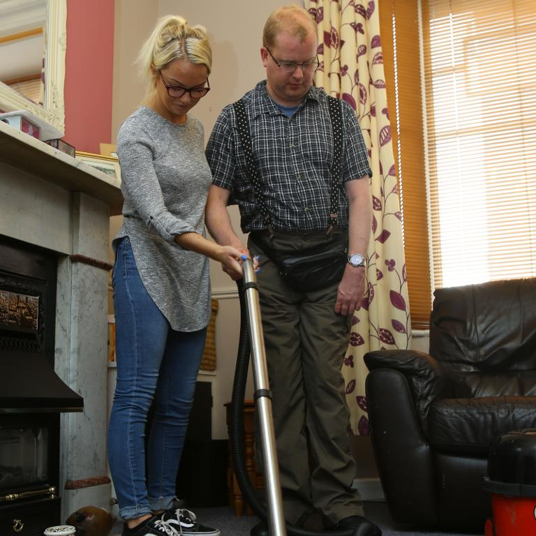 A support worker helps a service user to vacuum the floor