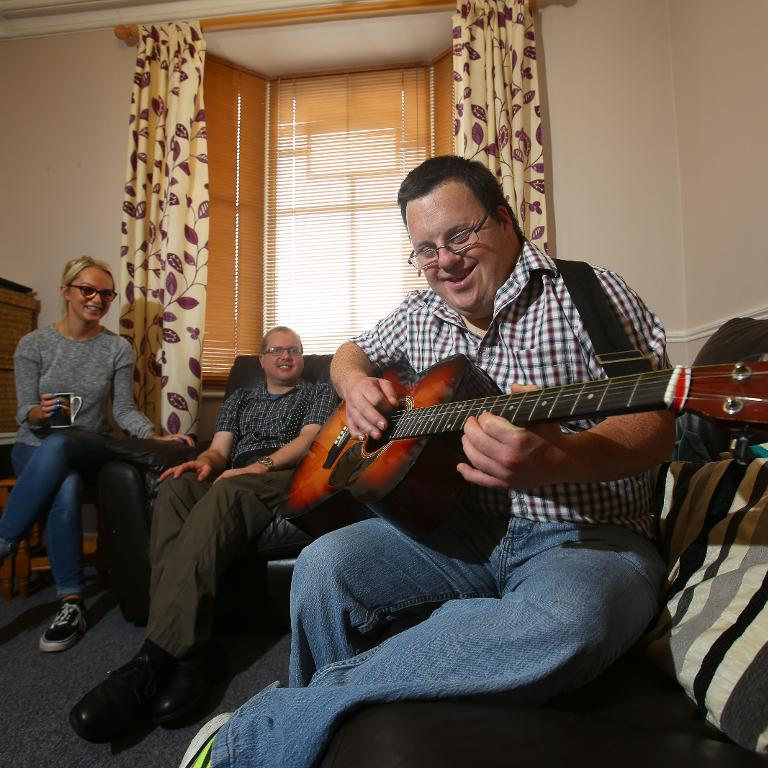 A service user entertains others by playing guitar